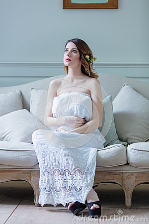 Free Young Pregnant Woman In White Dress Sitting Stock Images - 105272354
