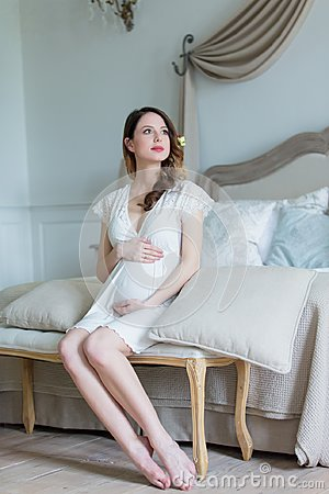 Free Young Pregnant Woman In White Dress Sitting Royalty Free Stock Photo - 105272365