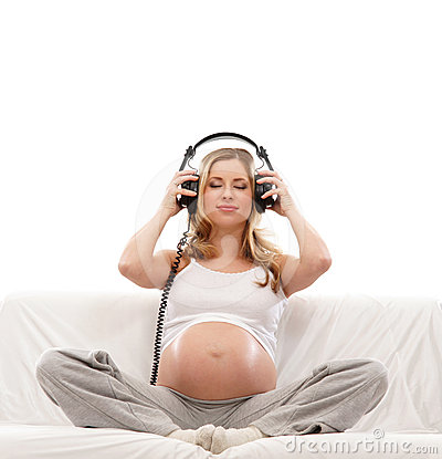 A young pregnant woman listening to the music