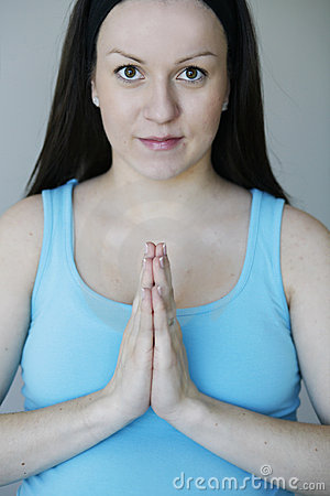 Young pregnant woman in meditative pose eyes open.