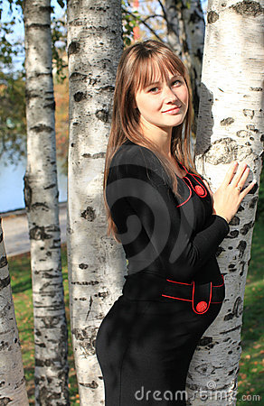 Young pregnant woman near birch