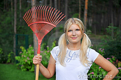 Young pretty gardening woman with rakes