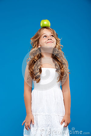Free Young Pretty Girl Holding Apple  On Head Over Blue Background. Stock Images - 75154794