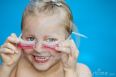 Young pretty girl in swimming-pool holding googles