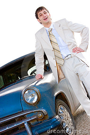 Young pretty man standing near old car