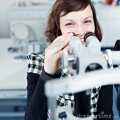 Young pretty optometrist using a slit lamp