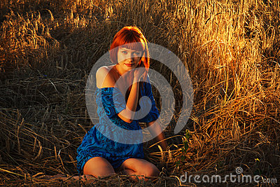 Young pretty red woman at the field
