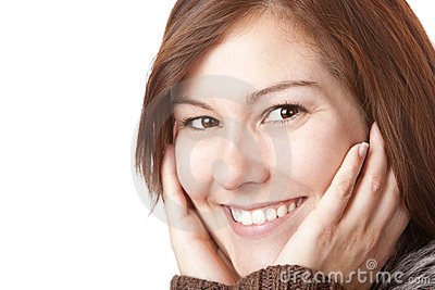 Young, pretty smiling woman with hands on face