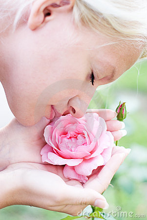 Young pretty woman enjoys  smell of  pink rose