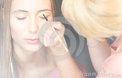 Young pretty woman getting make-up with brush.