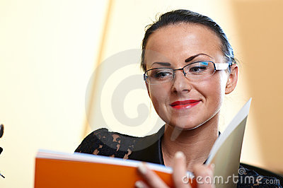 Young pretty woman with orange book in hands