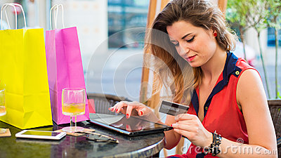 Young pretty woman with pad holding credit card.She is siting in cafe.