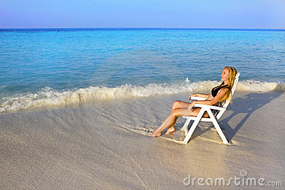 Young pretty woman tans in beach chair  in ocean