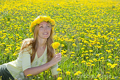 Young pretty woman in wreath of dandelions
