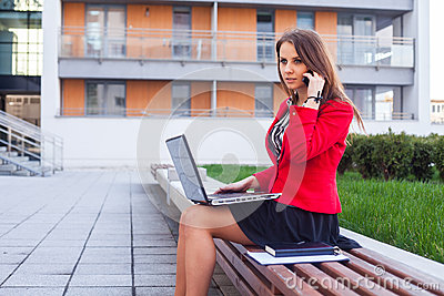 Young professional business woman sitting outdoor with computer