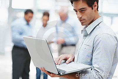 Young professional using a laptop with colleagues