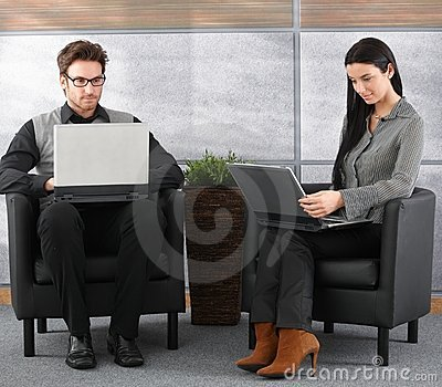 Young professionals in office lobby with laptop Stock Photo
