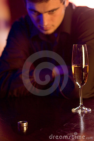 Young puzzled man with ring and champagne glass in restaurant