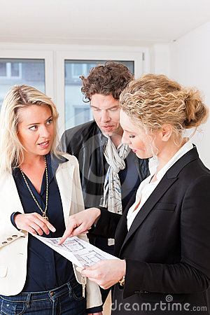 Young realtor explains lease agreement to couple