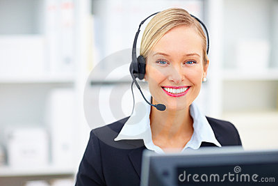 Young receptionist smiling in office using headset