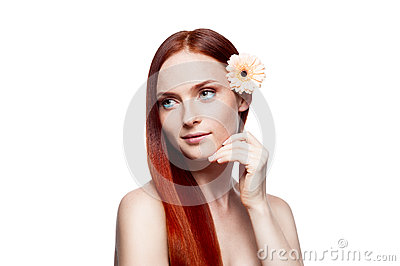 Young red-haired female with flower in hair