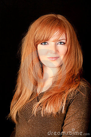 Young red-haired girl smiling on a dark background