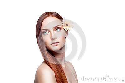 Young red-haired green-eyed female with flower