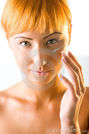 Young red-haired woman put cream on face
