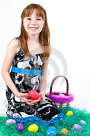 Young female sitting in fake grass with Easter eggs