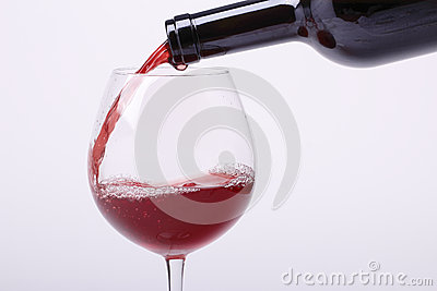 Young red wine is poured into a glass