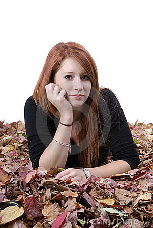 Young reddish woman lying in autumn leaves