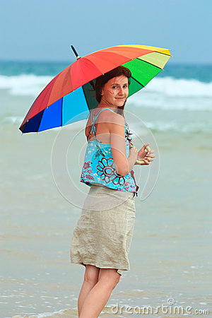 Young redhead on the beach with a rainbow umbrella