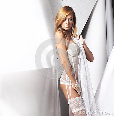 A young redhead Caucasian woman in white lingerie