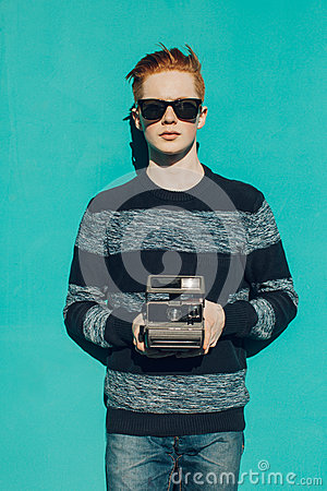 Free Young Redhead Man In A Sweater And Jeans And Sunglasses Standing Next To Turquoise Wall And Taking Photos Vintage Camera Warm Summ Royalty Free Stock Photography - 53745487
