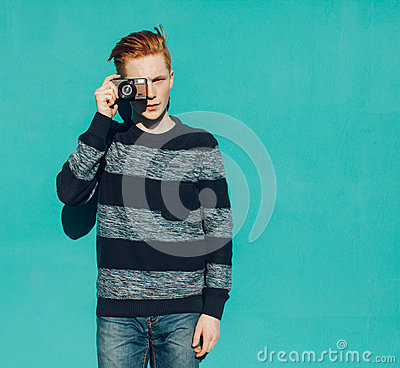 Free Young Redhead Man In A Sweater And Jeans Standing Next To Turquoise Wall And Taking Photos Vintage Camera Warm Summer Sunny Day Royalty Free Stock Images - 53745469
