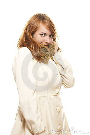 Young redhead woman covering her face in fawn wint
