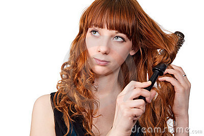 Young redhead woman straightening her hair