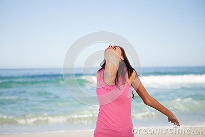 Young relaxed woman standing on the beach with her arms spread