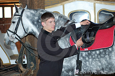 Young rider tightens a saddle-girth
