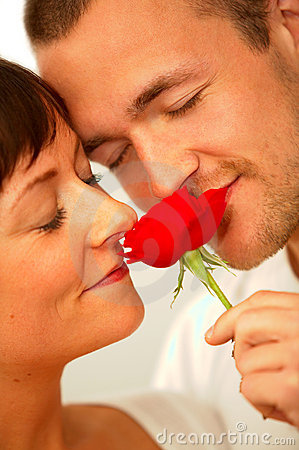 A young romantic couple enjoying the scent of a rose