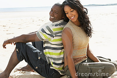 Young Romantic Couple Relaxing On Beach Together