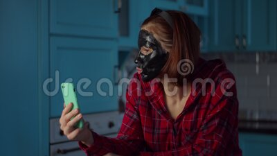 Young 30s woman with black cosmetic mask on her face using mobile phone, having video call at home. Woman beauty routine. With gadget on kitchen stock video footage