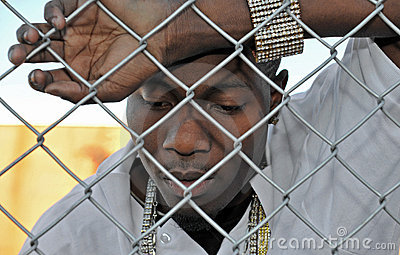 Young sad black man behind a fence.