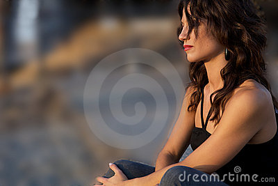 Young sad woman sitting by herself
