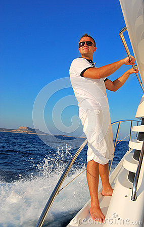 Young Sailor relaxing happily on the vacation sailboat yach