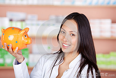Young saleswoman in pharmacy holding piggy bank
