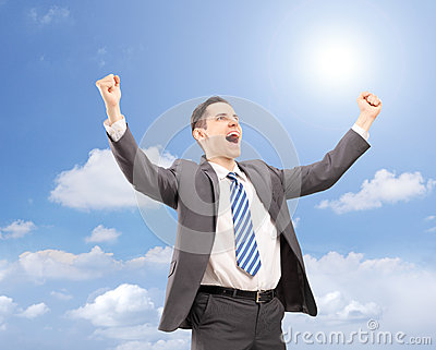 Young satisfied businessman gesturing happiness against blue sky