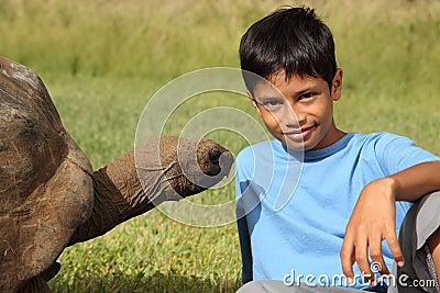 Young school boy sitting alongside giant tortoise