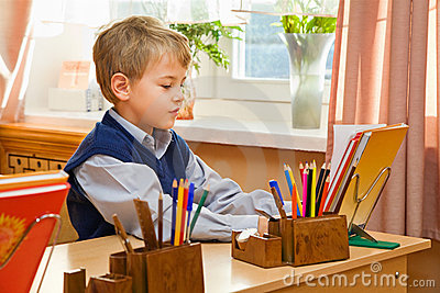 Young schoolboy sitting Behind a school desk