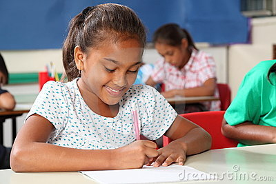 Young schoolgirl in classroom busy writing at desk